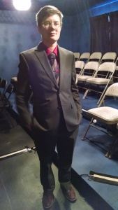 A young trans man stands in an empty, small theater space with a chandelier behind them. They wear a grey suit, brown and grey striped neck tie, and a tie clip with a red heart over a red shirt. They are smiling gently.