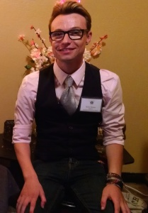 A young wearing a black vest and silver tie over a light pink shirt sits in front of a vase of flowers.