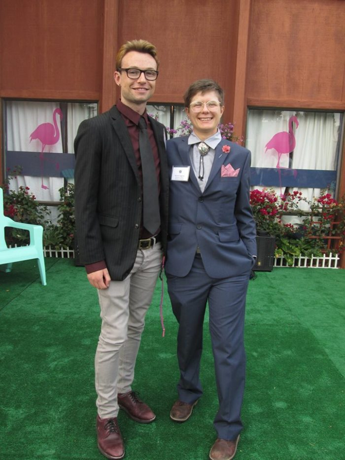 Two young gentlemen stand on a grassy patio in front of a building with pink flamingos in the window. Reilly, on the viewer's left, wears a black blazer and tie over a maroon shirt. Marrok, on the viewers right, wears a blue suit with a bolo tie and red flower and pocket square.